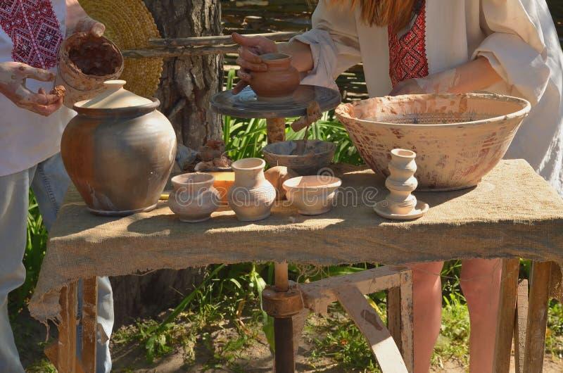 En keramiker som gör en leratillbringare på gammalt trä royaltyfri fotografi