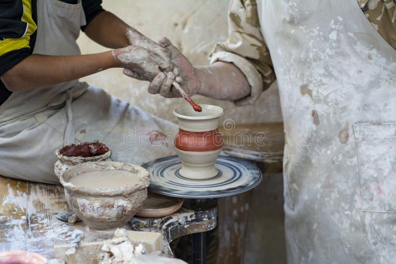 En keramiker undervisar ett barn royaltyfri foto