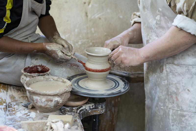En keramiker undervisar ett barn arkivfoton