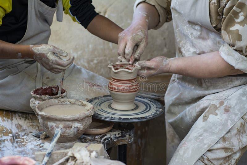 En keramiker undervisar ett barn royaltyfri bild