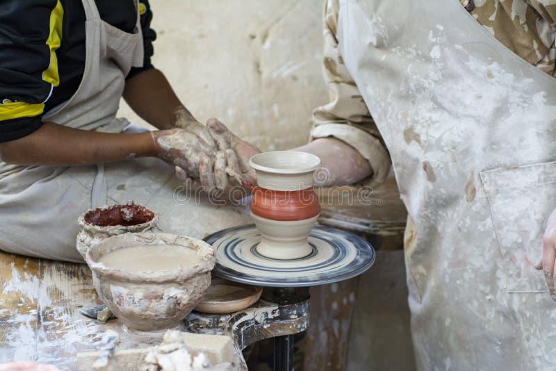 En keramiker undervisar ett barn royaltyfria foton