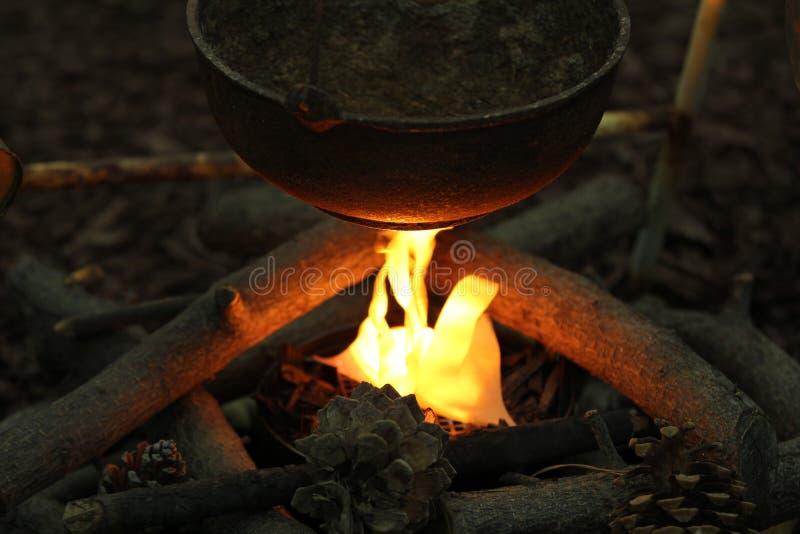 En kettlekruka över en campfire. arkivfoton