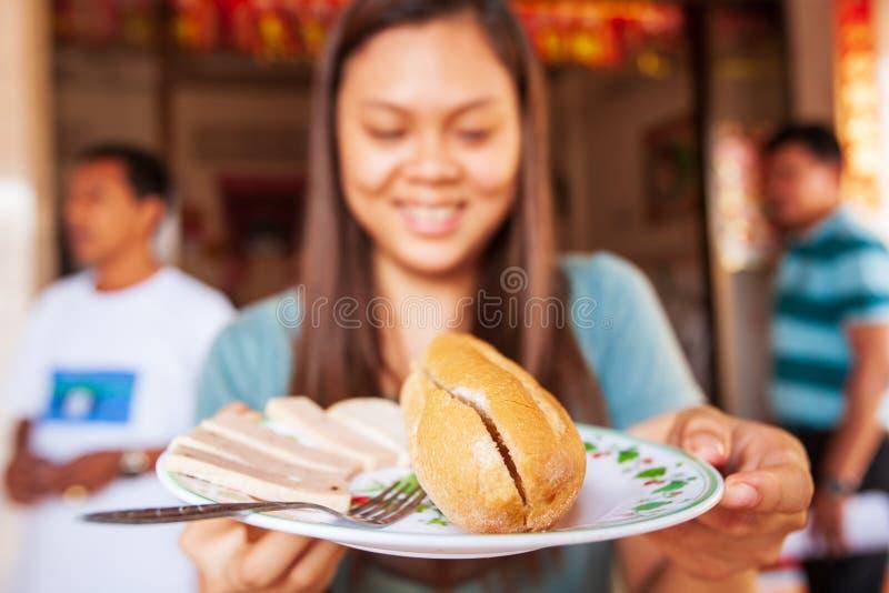 En khmerkvinnor som ler och rymmer maträtten med bagetten Bagett eller royaltyfria bilder