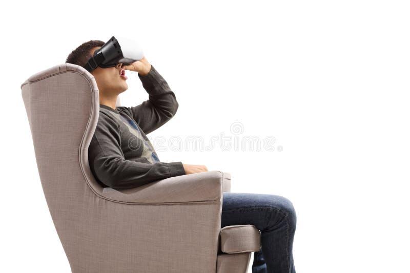 En kille i en armstol som använder ett headset för virtuell verklighet royaltyfri fotografi