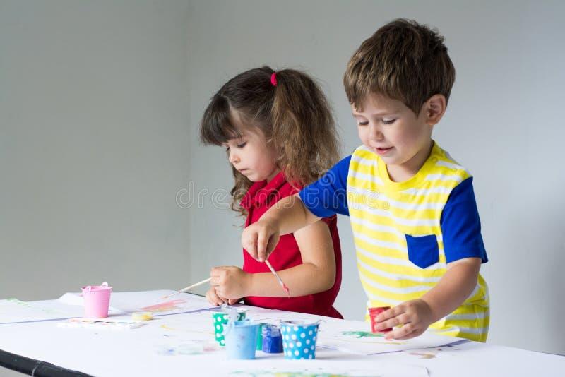 En kinderen thuis of kleuterschool of playschool die spelen schilderen stock foto