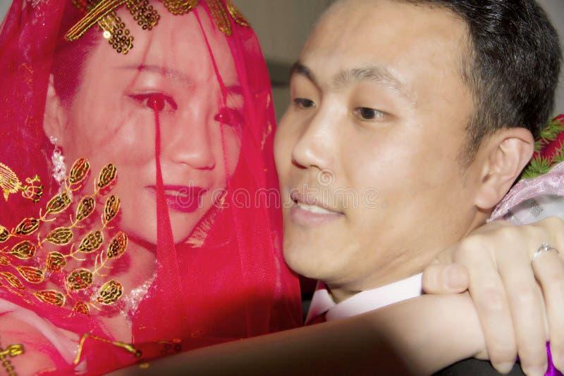 En kinesisk brudgum rymmer hans brud med armar arkivfoto