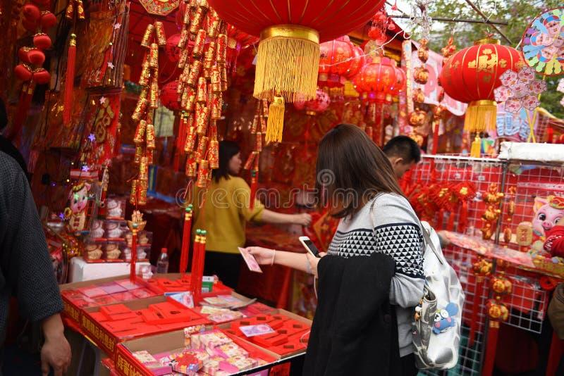 En kinesisk kvinna köper hantverk på den kinesiska marknaden för det nya året fotografering för bildbyråer