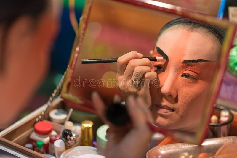 En kinesisk maskering för operaaktrismålning på hennes framsida för kapaciteten på i kulisserna på den viktiga relikskrin i Bangk royaltyfria bilder