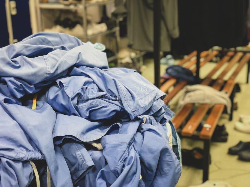 En kläderkorg som flödar över med kirurgiskt, skurar i det ändrande rummet av ett sjukhus i Förenade kungariket - slarvig miljö a royaltyfri foto