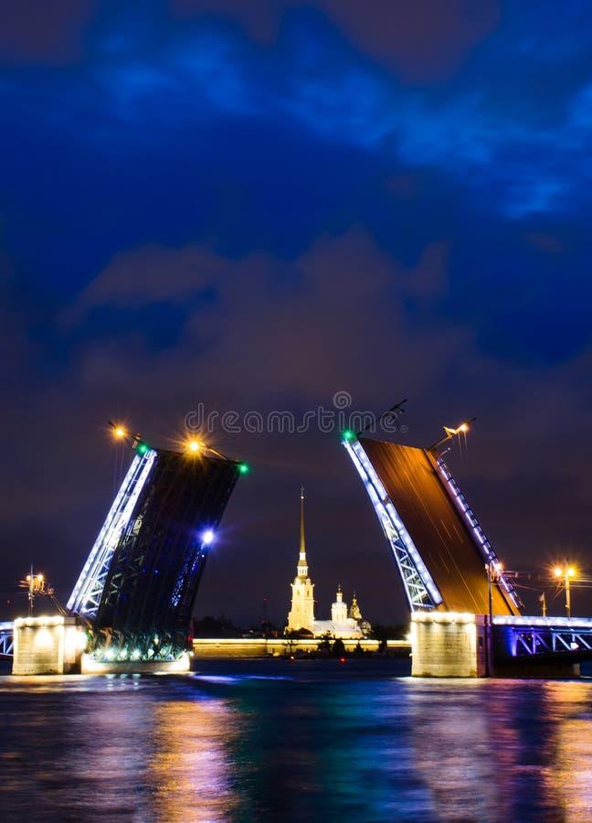 En klaffbro av St Petersburg på natten med en fästning mellan den royaltyfria bilder