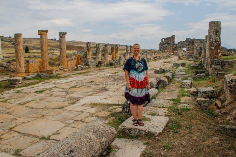 En klassisk antik grekisk teater i Pamukkale, Denizli, Turkiet och en vit ung kvinna i en hippieklänning arkivfoto