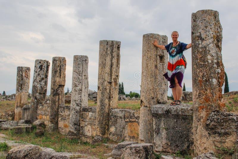 En klassisk antik grekisk teater i Pamukkale, Denizli, Turkiet och en vit ung kvinna i en hippieklänning royaltyfri bild