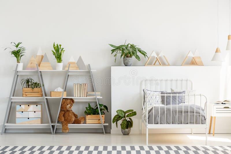 En klassisk barnsovruminre med enkelt scandinavian stilmöblemang och en grå träbokhylla med en nallebjörn fotografering för bildbyråer