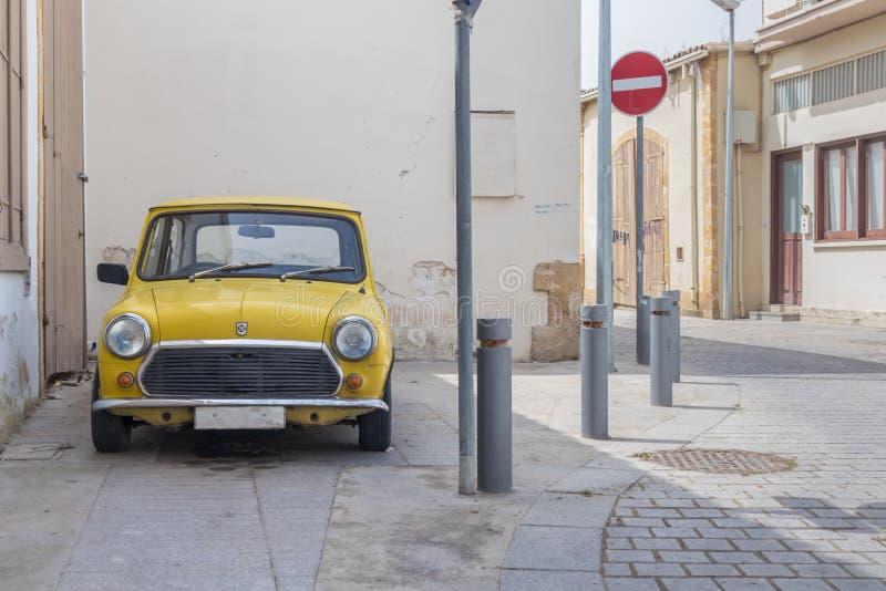 En klassisk gul mini- tunnbindare parkerade royaltyfri bild