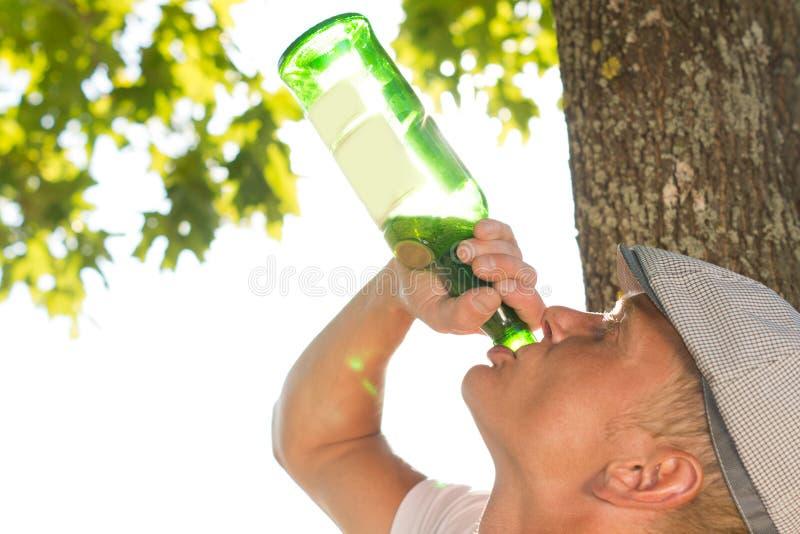En knarkare som dricker från en flaska av vin royaltyfria foton