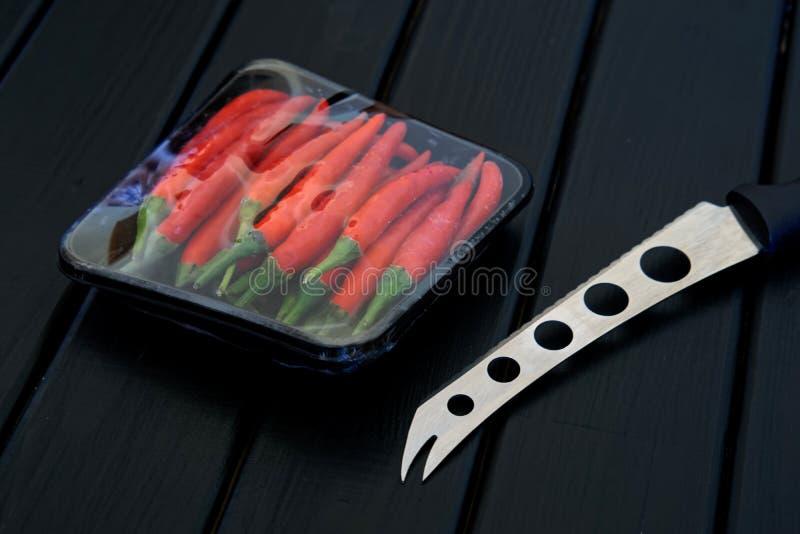 En kniv för ost och grönsaker, tillsammans med en packe av peppar för röd chili, lögn på en svart träyttersida royaltyfri bild
