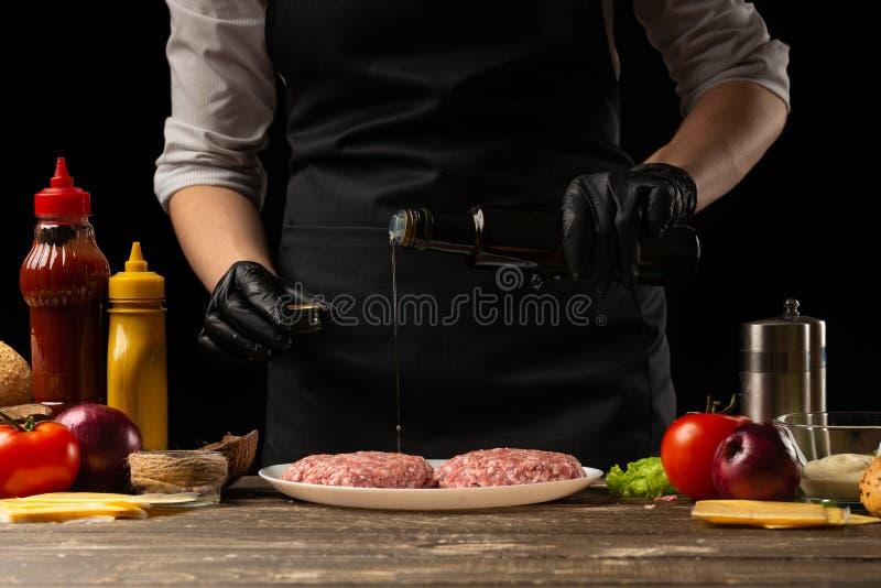 En kock förbereder att bevattna nötkötthamburgare med smör, på en bakgrund med ingredienser, restaurangaffären, snabbmat, smaklig arkivbilder