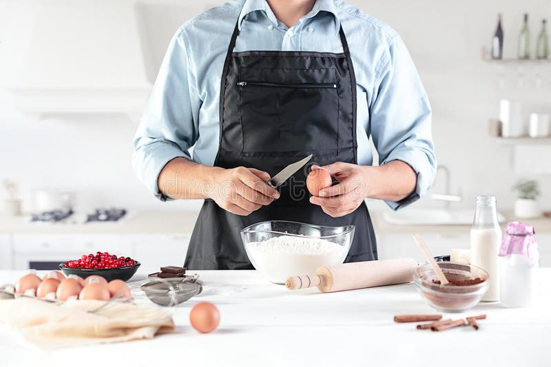 En kock med ägg på ett lantligt kök mot bakgrunden av händer för man` s royaltyfri fotografi