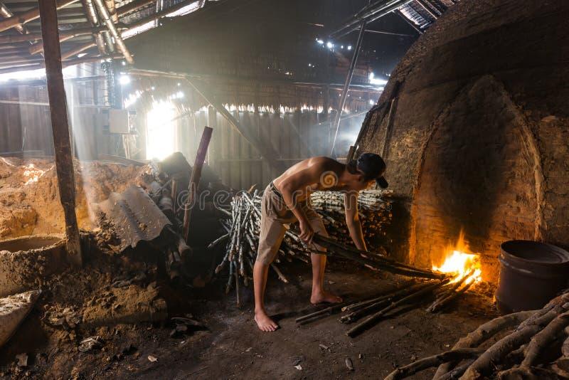 En kolarbetare på arbete på en hög av den långsamma brinnande wood charcoaen royaltyfria foton