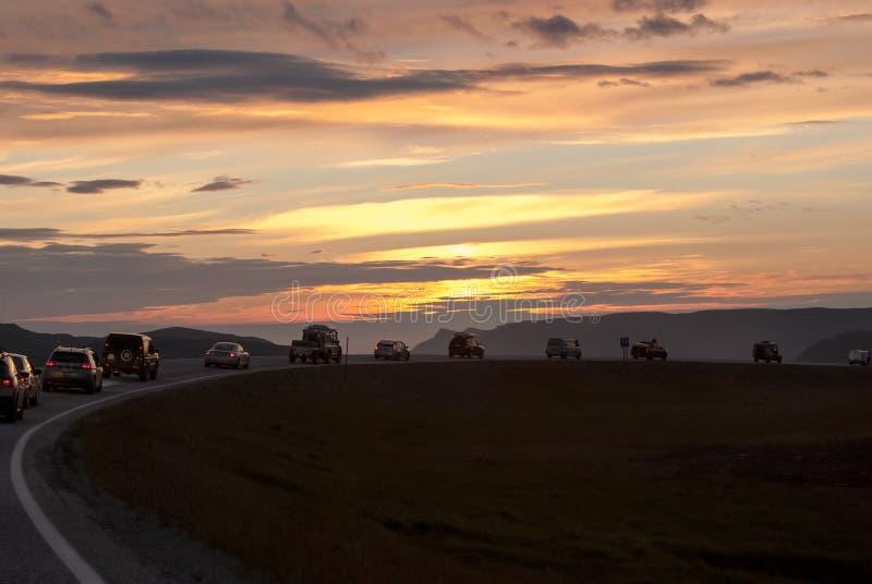 En kolonn av bilar på en slingrig väg på solnedgången, Mageroya ö, Norge fotografering för bildbyråer