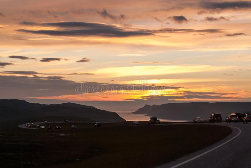En kolonn av bilar på en slingrig väg på solnedgången, Mageroya ö, Norge arkivfoto