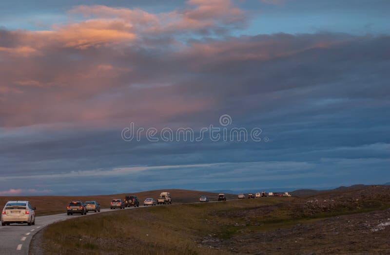 En kolonn av bilar på en slingrig väg på solnedgången, Mageroya ö, Norge royaltyfri fotografi
