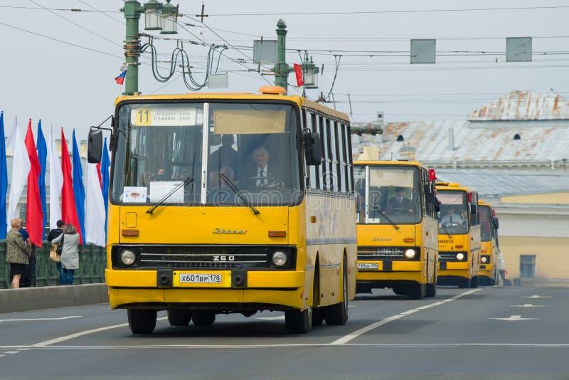 En kolonn av gula ungerska bussar p? slottbron fotografering för bildbyråer