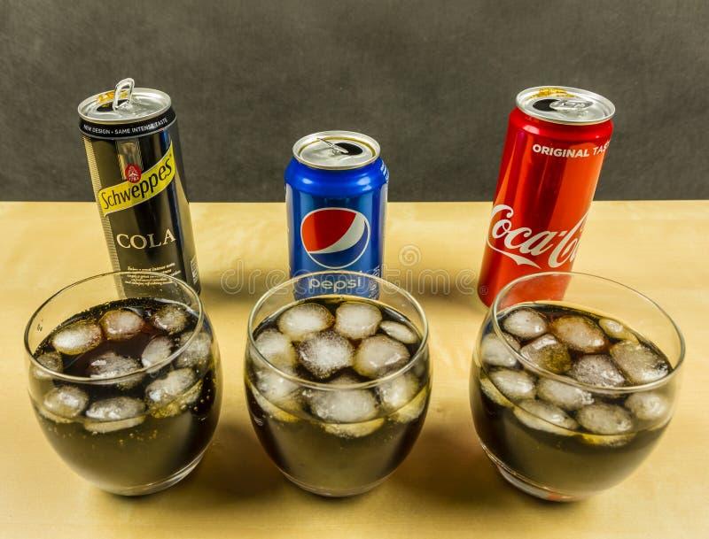 En kolsyrad drink för cola som göras av Pepsi, cocaen - cola och Schweppes framlagt i exponeringsglas med iskuber fotografering för bildbyråer