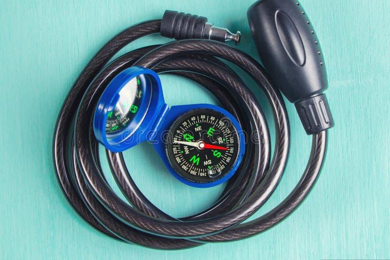 En kompass och ett cykellås på en grön träbakgrund arkivfoton