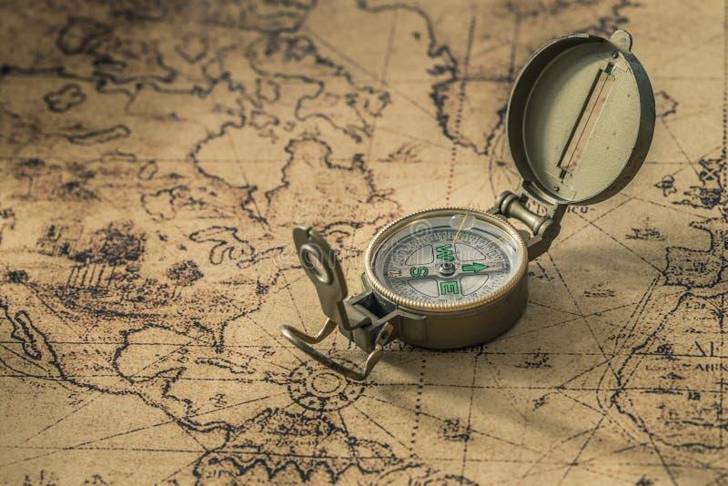 En kompass på en gammal översikt som visar riktningen arkivfoton
