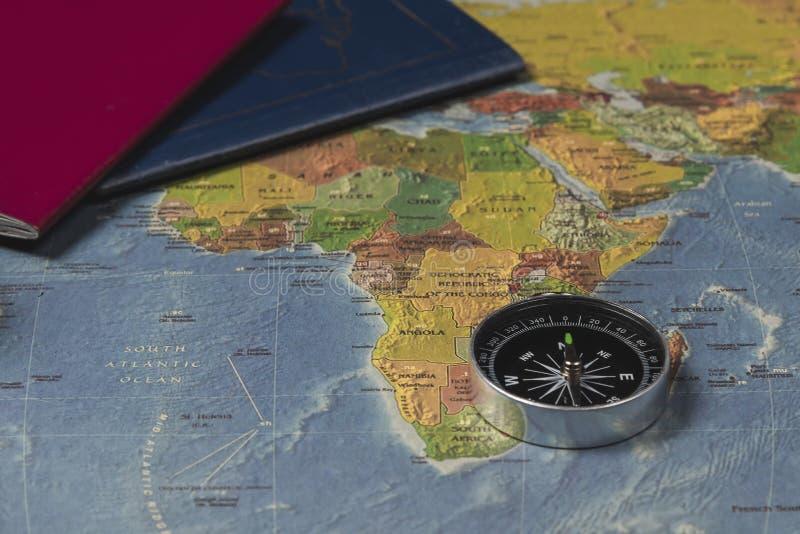 En kompass på världskartan och pasportsna royaltyfri fotografi