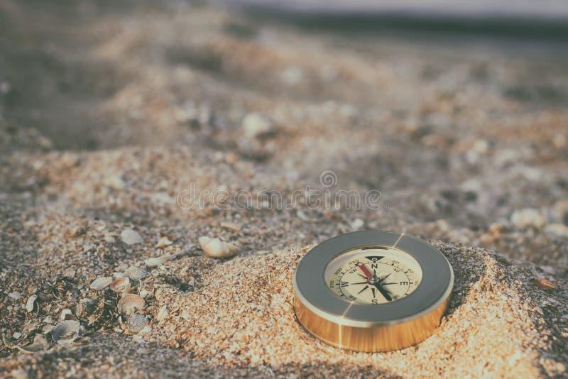 En kompass som visar riktningen, ligger på havssanden med skal arkivbilder