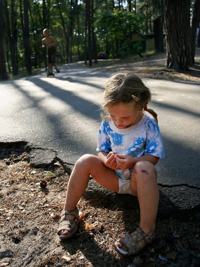 En koncentrerad liten flicka med ett skrapat knä sitter på asfalten i sommaren royaltyfri foto