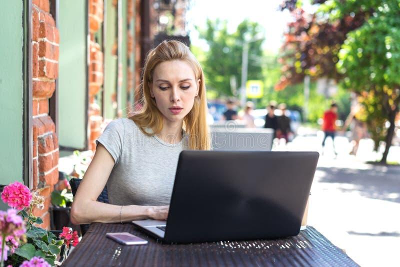 En koncentrerad självständig Caucasian kvinna som arbetar med hennes telefon och bärbar dator i en restaurangterrass arkivfoto