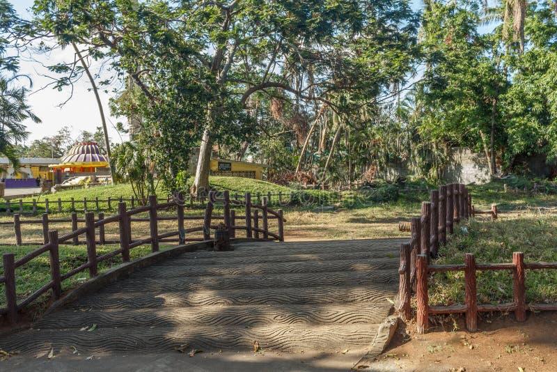 En konkret ärke- bro med träservice av sidan som leder in mot trädgården, Chennai, Tamil Nadu, Indien, Januari 29 2017 arkivfoto