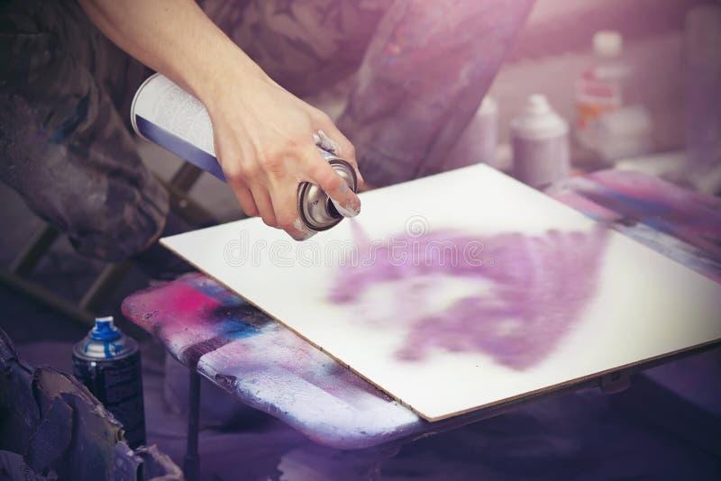 En konstnär drar på en vit kanfas med en rosa sprutmålningsfärggrafitti royaltyfri foto