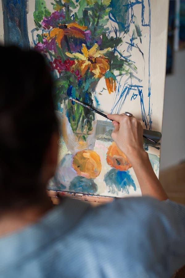 En konstnär för ung kvinna målar en oljamålning på staffli fotografering för bildbyråer