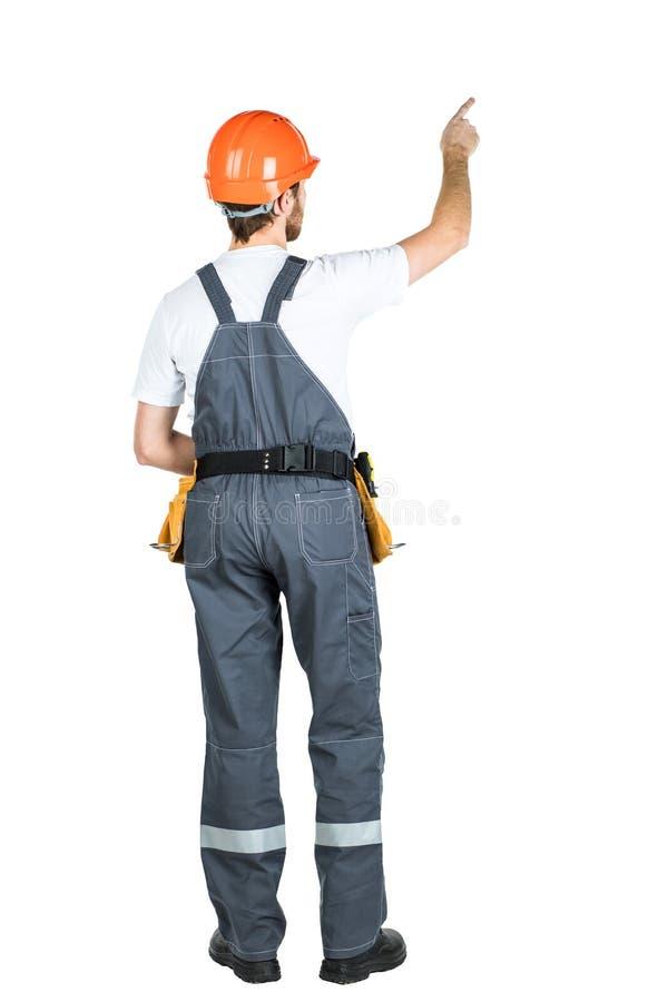 En konstruktionsman står med hans baksida och visar hans hand Repa royaltyfri bild