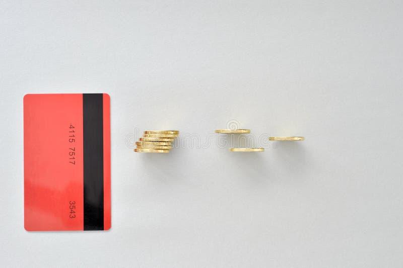 En kontokort i färgen av att bo korall med skinande gula mynt som symboliserar elektronisk betalning arkivfoto