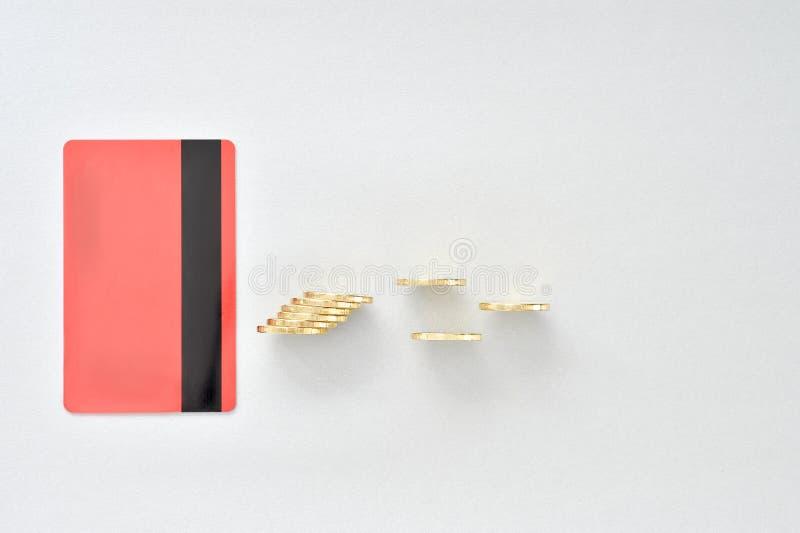 En kontokort i färgen av att bo korall med skinande gula mynt som symboliserar elektronisk betalning royaltyfria bilder