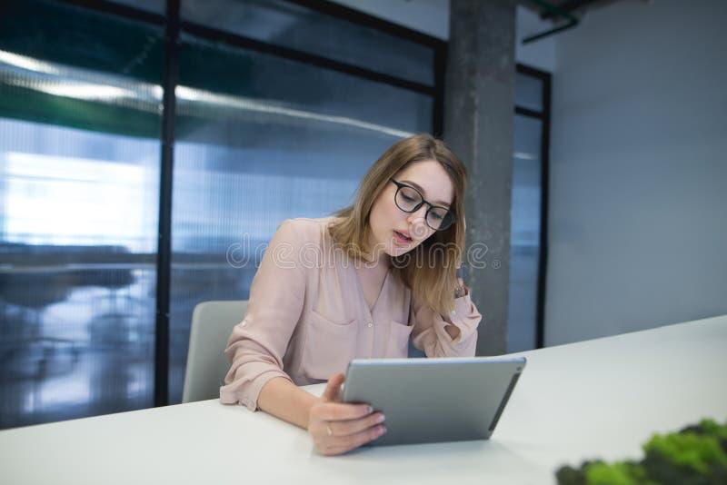 En kontorsarbetare använder en tabell som sitter på, saltar i kontoret Stilfullt arbete på en coworking minnestavla arkivfoton