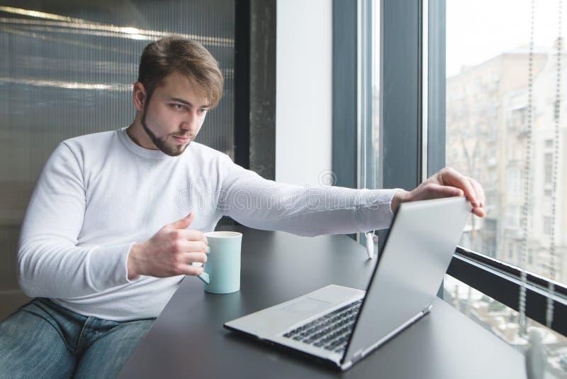 En kontorsarbetare med en kopp av den varma drinken i hans händer börjar att arbeta på en bärbar dator royaltyfria bilder