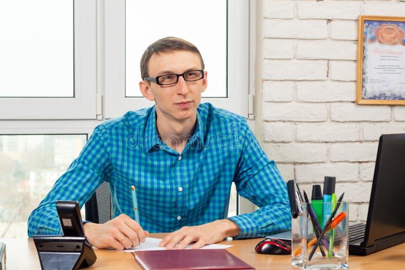 En kontorsarbetare ser besökaren med en fundersam blick arkivbilder