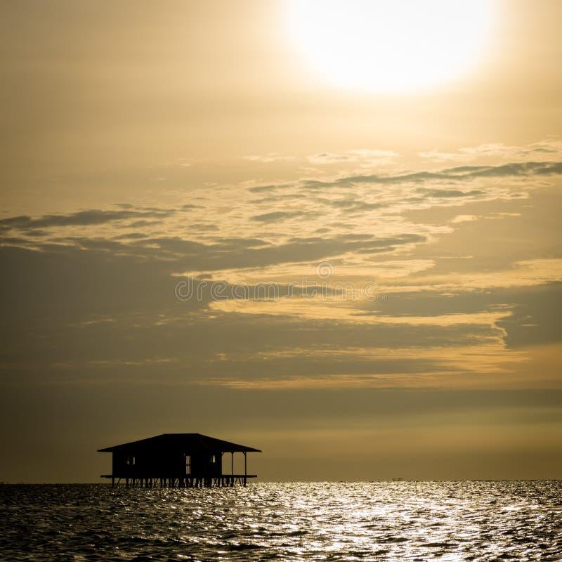 En kontur av den traditionella sväva stugan som som överges av invånare av den Harapan ön med härlig orange himmel fotografering för bildbyråer