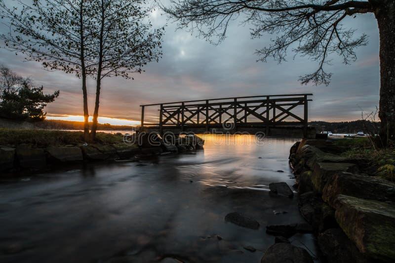 En kontur av en liten träbro som korsar en flod Mörk morgon tidig soluppgång i Lillesand, Norge arkivbild