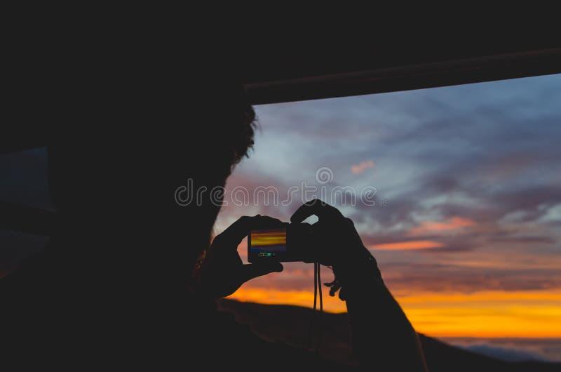 En kontur av en man som tar en bild arkivfoton
