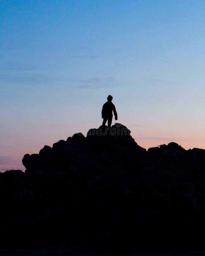 En kontur av en man under en vibrerande solnedgång royaltyfri fotografi