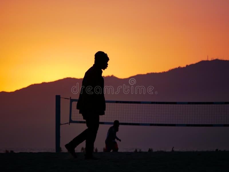En kontur för man` som s går av stranden under solnedgång royaltyfri foto