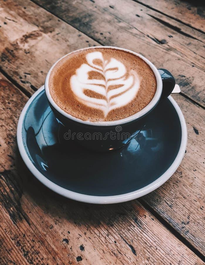 En kopp av cappuccino med lattekonst royaltyfria foton