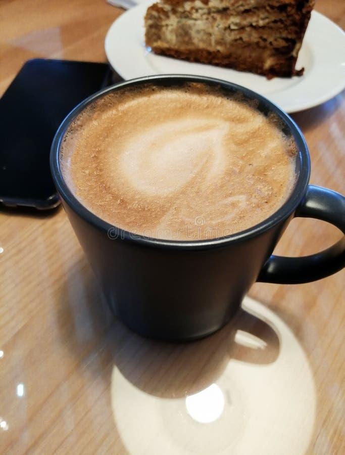 En kopp av cappuccinokaffe på en tabell i ett kafé bredvid dig kan se en platta med en brun kaka arkivbilder